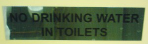 "Schild das den Spruch ""NO DRINKING WATER IN TOILETS\"" zeigt"
