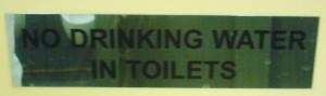 """Schild das den Spruch \""""NO DRINKING WATER IN TOILETS\"""" zeigt"""